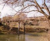 Puente negro sobre un río esmeralda