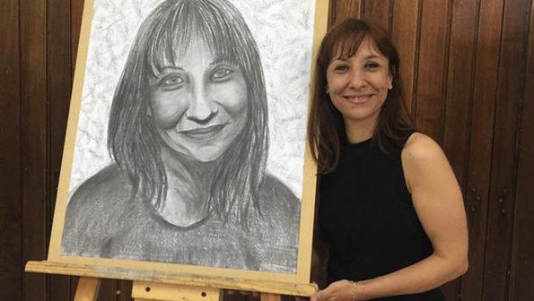 Adriana Garbarino, una de las artistas piquenses seleccionadas, posa junto a un regalo de su alumna del ISBA, Andrea Correa
